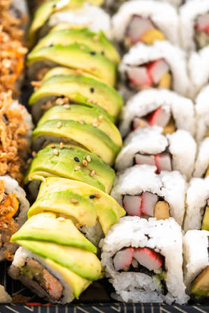 Pre-packaged variety of sushi and sushi rolls in a plastic tray. Archivio Fotografico