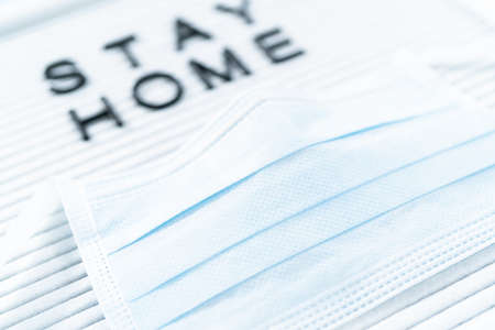 STAY HOME sign on message board with a blue medical mask.