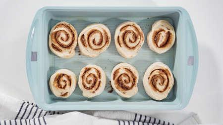 Flat lay. Unbaked cinnamon rolls in a blue baking pan.