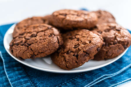 Freshly baked double chocolate chip cookies on a white plate. Archivio Fotografico