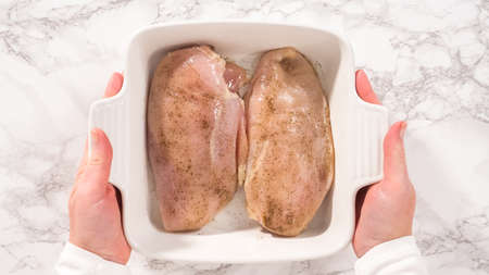 Flat lay. Step by step. Seasoning chicken with salt and pepper for baking in a baking dish.
