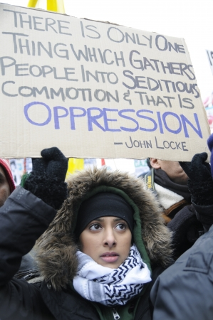TORONTO - JANUARY 10  A teenage Arab girl holding a banner of a famous quote from John Locke, during a rally to condemn the Israel occupation on Gaza on January 10 2009 in Toronto, Canada