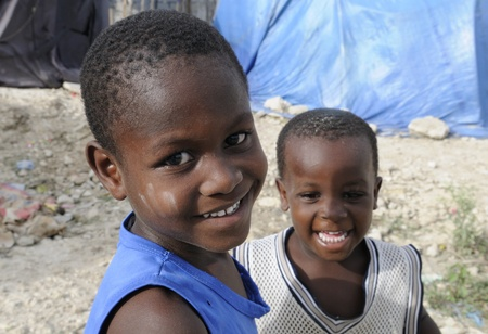 PORT-AU-PRINCE - AUGUST 28: Two unidentified kids sharing a laugh in one of the Tent Cities in Haiti, on August 28, 2010 in Port-Au-Prince, Haiti
