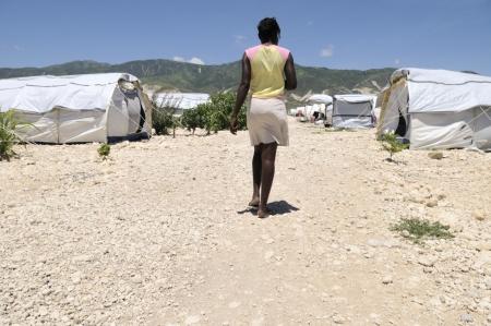 ポルトープランス-8 月 30 日: 2010 年 8 月 30 日にポルトープランス、ハイチのテント都市のいずれかで彼女のテントに向かって歩いてハイチ女の子。