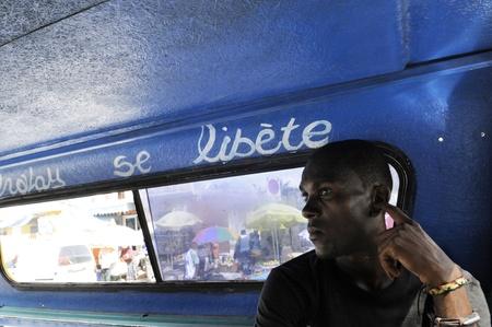 port au prince: PORT-AU-PRINCE - 31 DE AGOSTO: Un preocupado buscando adulto joven haitiano se sienta dentro de un tap-tap-el modo m�s barato de, Port-Au-Prince, Hait� el 31 de agosto de 2010. Editorial