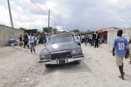 hearse: PORT-AU-PRINCE -SEPTEMBER 1:A hearse waiting outside the camp acra during a funeral of a 6 months old baby - burnt alive inside his tent while asleep on September 1 2010 in Port-Au-Prince,Haiti.