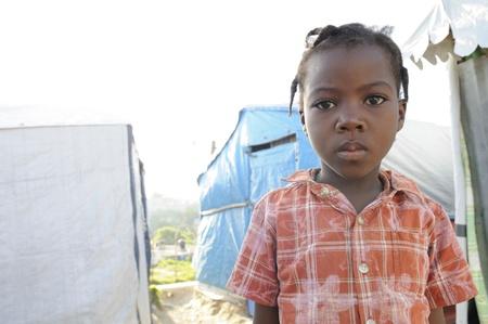 ポルトープランス-9 月 2 日: 未確認ハイチの子供 2010 年 9 月 2 日にポルトープランス、ハイチで彼女のテント都市通路でカメラにポーズします。 報道画像
