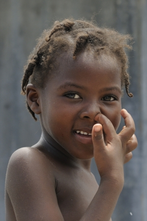 PORT-AU-PRINCE - SEPTEMBER 2: An unidentified Haitian children cleaning her nose in front of her tent in Port-Au-Prince, Haiti on September 2, 2010.