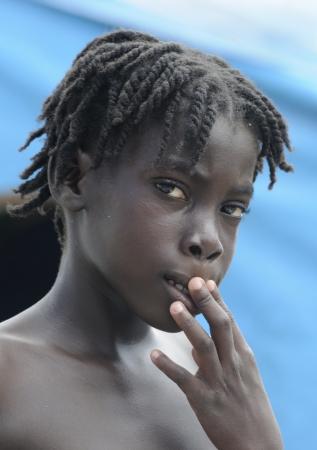 PORT-AU-PRINCE - SEPTEMBER 2: An unidentified Haitian kid biting her lips, in Port-Au-Prince, Haiti on September 2, 2010.