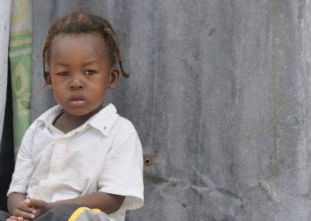 port au prince: PORT-AU-PRINCE - 02 de septiembre: Un ni�o haitiano no identificado sentado en la puerta de su tienda, en Port-au-Prince, Hait� el 2 de septiembre de 2010. Editorial