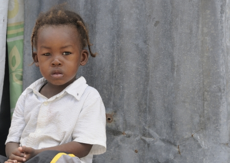 PORT-AU-PRINCE - SEPTEMBER 2: An unidentified Haitian Child sitting on the doorstep of her tent , in Port-Au-Prince, Haiti on September 2, 2010.