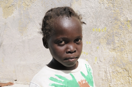 PORT-AU-PRINCE - SEPTEMBER 2: An unidentified Haitian girl standing in front of her survived building in Port-Au-Prince, Haiti on September 2, 2010.