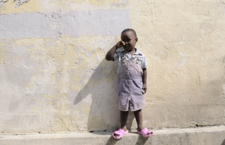 PORT-AU-PRINCE - SEPTEMBER 2: An unidentified Haitian kid crying in front of his house , in Port-Au-Prince, Haiti on September 2, 2010.
