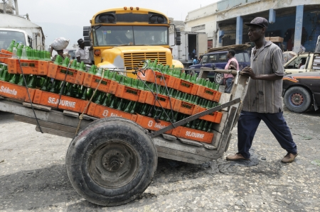 PORT-AU-PRINCE - AUGUST 21: A man carrying empty crates of drinks on a cart in the Iron Market in Port-Au-Prince, Haiti on August 21, 2010.