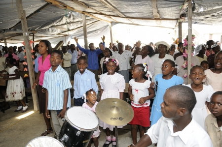 CARREFOUR - AUGUST 22: People performing their sunday prayers inside a tent, which used to be church before the earthquake ,in Carrefour Haiti on August 22, 2010.