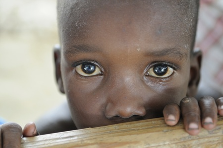 PORT-AU-PRINCE - AUGUST 22: An unidentified poor Haitian kid looking with surprise towards the photographer during a food camp ,in Port-Au-Prince, Haiti on August 22, 2010. Editorial