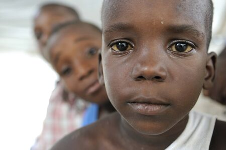 PORT-AU-PRINCE - AUGUST 22: unidentified Haitian kids looking over the shoulder of each other during a food distribution camp in Port-Au-Prince, Haiti on August 22, 2010.