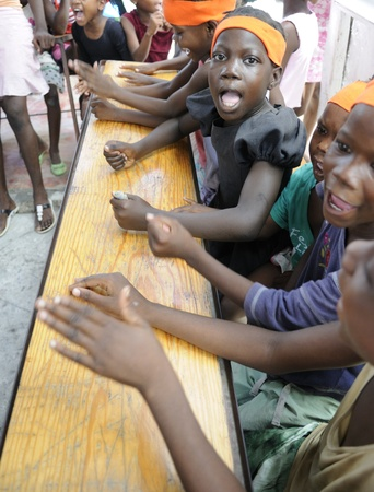 PORT-AU-PRINCE - AUGUST 25: unidentified Kids banging their desks while singing their prayer in on of a local school in Cite Soleil- in Port-Au-Prince, Haiti on August 25, 2010.