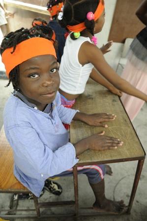 port au prince: PORT-AU-PRINCE - 25 de agosto: Un ni�o no identificado haitiana mirando a la c�mara mientras estudiaba en una peque�a escuela en Cit� Soleil, en Port-au-Prince, Hait� el 25 de agosto de 2010.
