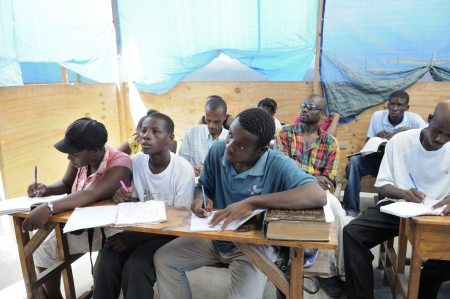 soleil: CITE SOLEIL-AUGUST 25: Students taking notes in a basic english class in a community school in Cite Soleil- one of the poorest area in the Western Hemisphere on August 25 2010 in Cite Soleil, Haiti.