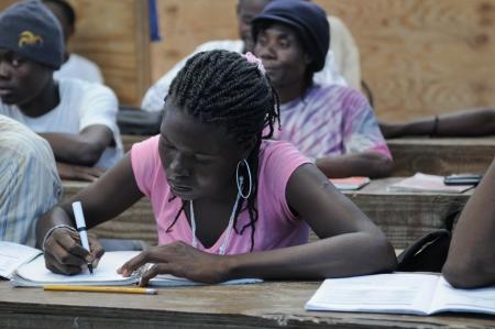 port au prince: Cit� Soleil-25 de agosto: Un estudiante tomando notas en una escuela de la comunidad local en Cit� Soleil, una de las zonas m�s pobres del hemisferio occidental, el 25 de agosto de 2010 en Cit� Soleil, Hait�.