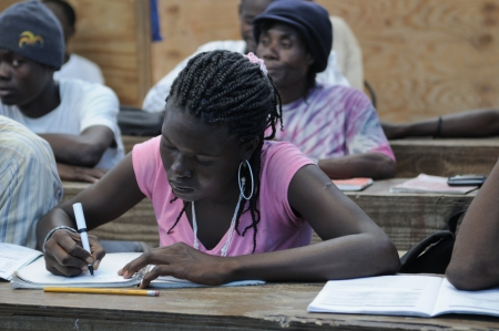CITE SOLEIL- AUGUST 25: A female student taking notes in a local community school in Cite Soleil- one of the poorest area in the Western Hemisphere on August 25 2010 in Cite Soleil, Haiti.