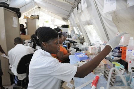 haematologists: PORT-AU-PRINCE - AUGUST 26: A Haitian health worker doing tests in a temporary tent lavatory on August 26 2010 in Port-Au-Prince, Haiti.