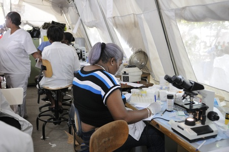 PORT-AU-PRINCE - AUGUST 26: An Haitian pathologist testing blood samples of patients in a temporary pathological tent on August 26 2010 in Port-Au-Prince, Haiti.
