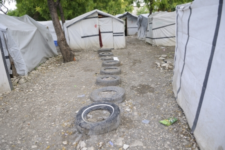 PORT-AU-PRINCE - AUGUST 26: Series of tires in front of the tents as a walkway to be used during heavy rainfall,in Port-Au-Prince, Haiti on August 26, 2010.