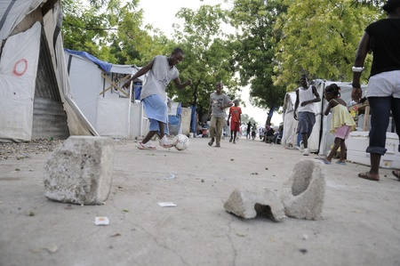 PORT-AU-PRINCE - AUGUST 26: Young residents playing soccer in front of their tents in Port-Au-Prince, Haiti on August 26, 2010.