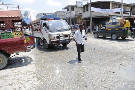 """port au prince: PORT-AU-PRINCE - 27 de agosto: Un viajero de ejecuci�n despu�s de """"Tap-Tap"""", que es la forma m�s com�n y barata de transporte en Hait�. en Port-Au-Prince, Hait� el 27 de agosto 2010"""