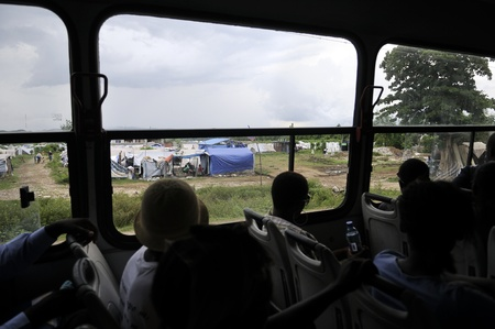 tent city: LEOGANE - AUGUST 27: People looking through the windows of a public bus towards a tent city, on August 27, 2010 in Leogane, Haiti