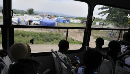 LEOGANE - AUGUST 27: A public bus passing by a tent city, on August 27, 2010 in Leogane, Haiti
