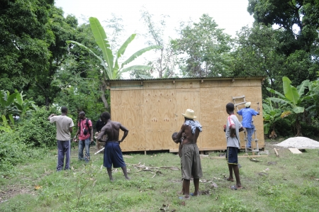LEOGANE - AUGUST 27: Residents watching a house being made by an NGO, on August 27, 2010 in Leogane, Haiti.