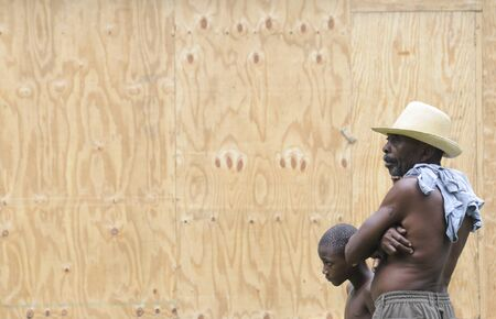 LEOGANE - AUGUST 27: A man and his son watching their house being made by an NGO, on August 27, 2010 in Leogane, Haiti. Editorial