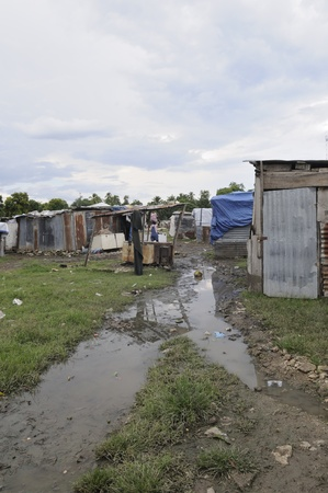 tent city: LEOGANE - AUGUST 27: A dirty tent city after a torrential  rainfall on August 27, 2010 in Leogane, Haiti