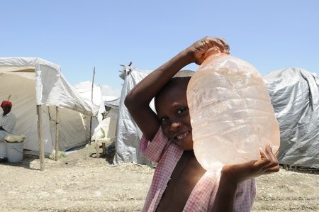 earthquake: PORT-AU-PRINCE - AUGUST 28: An unidentified young boy carrying a bottle of water after the water arrived in the tent city ,in Port-Au-Prince, Haiti on August 28, 2010.