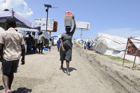 displaced: PORT-AU-PRINCE - AUGUST 28: A woman selling cold drinks during hot and humid afternoon in one of the tent cities in Port-Au-Prince, Haiti on August 28, 2010. Editorial