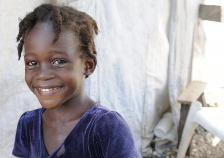 ni�os pobres: PORT-AU-PRINCE - 28 de agosto: Una chica joven de inter�s period�stico compartir una risa fuera de su tienda de campa�a en Port-Au-Prince, Hait� el 28 de agosto de 2010.