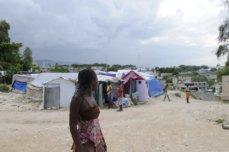 tent city: PORT-AU-PRINCE - AUGUST 28: An Young woman sharing a joke with other residents of the Tent City, on August 28, 2010 in Port-au-prince, Haiti