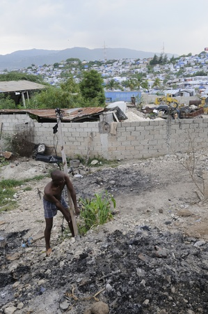 PORT-AU-PRINCE - AUGUST 28: A man trying to lift a pole ,in order to take it to some other place to built another tent for his family, on August 28, 2010 in Port-Au-Prince, Haiti Stock Photo - 15240234