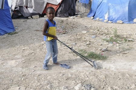 PORT-AU-PRINCE - AUGUST 28: A young unidentified kid playing beside his tent on August 28, 2010 in Port-Au-Prince, Haiti. Stock Photo - 15240259