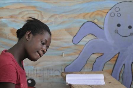 port au prince: Cit� Soleil-AGOSTO 25: Una estudiante que hace su trabajo de clase en una escuela de la comunidad local en Cite Soleil, una de la zona m�s pobre del hemisferio occidental el 25 de agosto de 2010 en Cit� Soleil, Hait�. Editorial