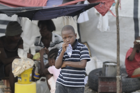 PORT-AU-PRINCE - AUGUST 26: A Haitian unidentified kid chewing a pouch packet of water on a hot afternoon, in Port-Au-Prince, Haiti on August 26, 2010. Stock Photo - 15240231