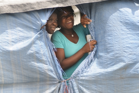 PORT-AU-PRINCE - SEPTEMBER 1:Camp residents peeping out through their tent window to watch a rally passing, in Port-Au-Prince, Haiti on September 1, 2010. Stock Photo - 15240157