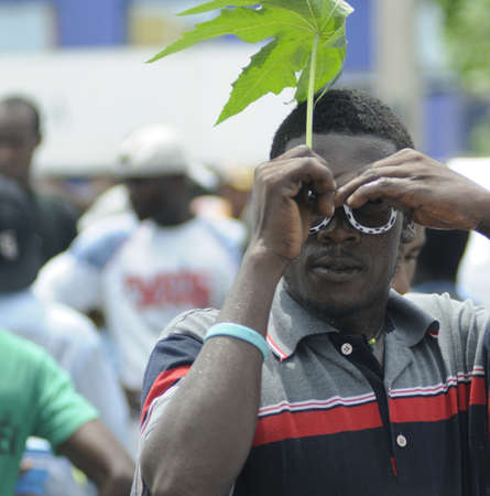 PORT-AU-PRINCE - SEPTEMBER 1: A Haitian teenager hiding his face from the photographer during a rally , in Port-Au-Prince, Haiti on September 1, 2010. Stock Photo - 15103467