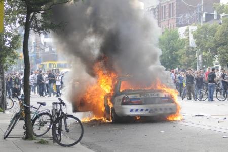 トロント-6 月 26: 警察は、抗議者はトロント、カナダで 2010 年 6 月 26 日に G20 の抗議の間にそれの周りに集まった一方女王と spadina の交差点に燃えて 報道画像