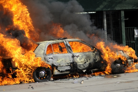 car crime: TORONTO-JUNE 26: Parts of a police car burning after being torched during the G20 Protest on June 26, 2010 in Toronto, Canada.