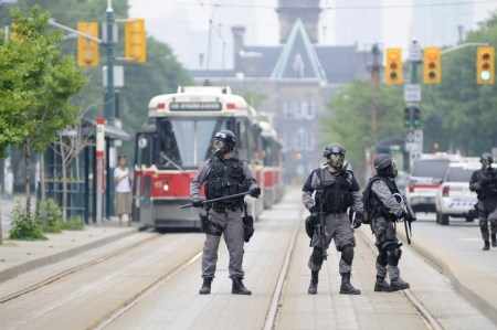 TORONTO-JUNE 27: Elite police personnel with gas masks protecting the street car tracks during the G20 Protest on June 27, 2010 in Toronto, Canada. Editorial