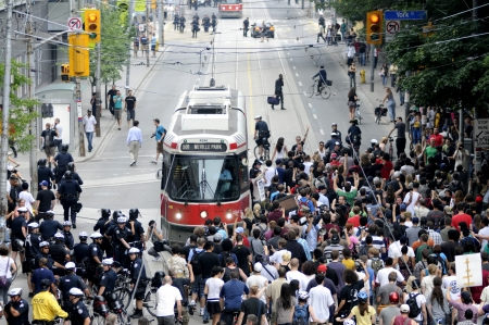 restricting: TORONTO-JUNE 28: Protesters clogging the downtown streets and restricting a passage for public transport during the G20 Protest on June 28, 2010 in Toronto, Canada.